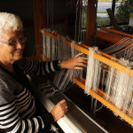 Kobi Brinkman demonstrates the begining of weaving at her loom.