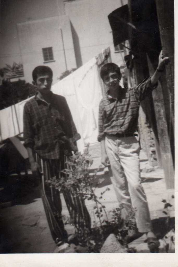 Romel Aziz (left) with young friend before he was forced to flee for the first time