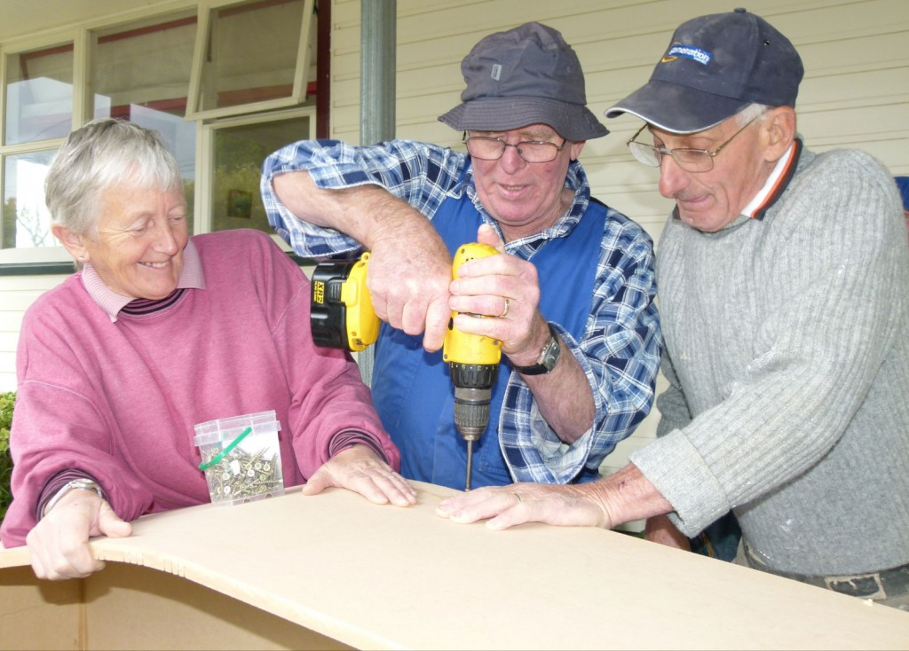 Well drilled: Volunteer builders Chris Mills, left, Graeme Lyford and Bill Sharpe drill on the coffin walls.