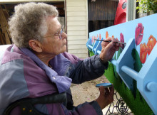 Finishing touches: Rose Gray paint tulips on her coffin to represent her Dutch heritage.